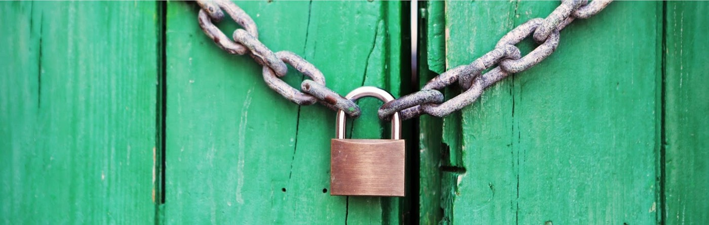 Green gate with padlock and chain.