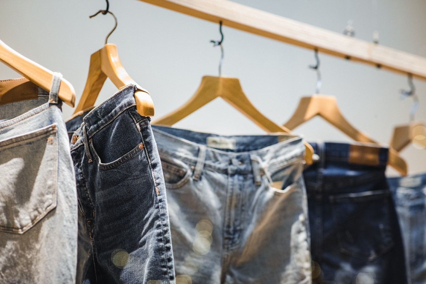 Several pairs of jeans on hangers.