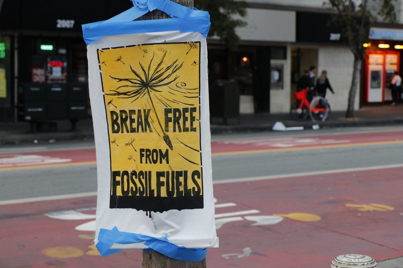 """A sign attached to a post that reads """"break free from fossil fuels""""."""