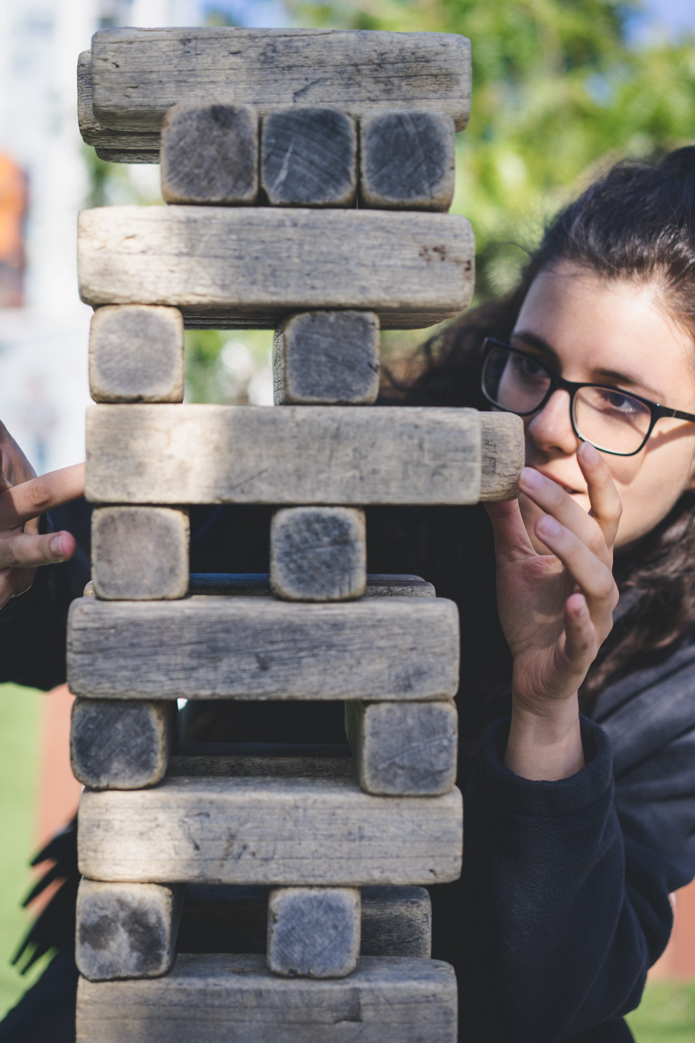 A young woman wearing glasses playing the game of Jenga with wooden sticks.