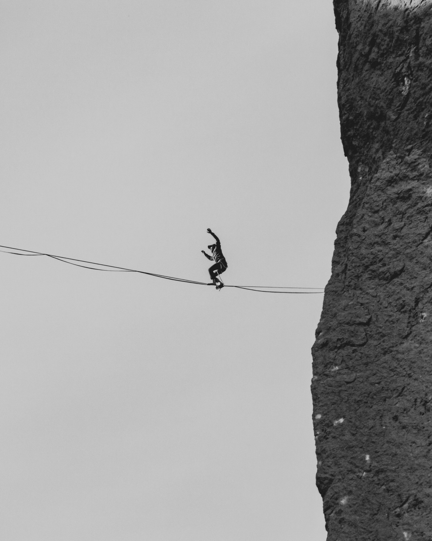 A tightrope walker focuses on keeping his balance as he makes his way across a void