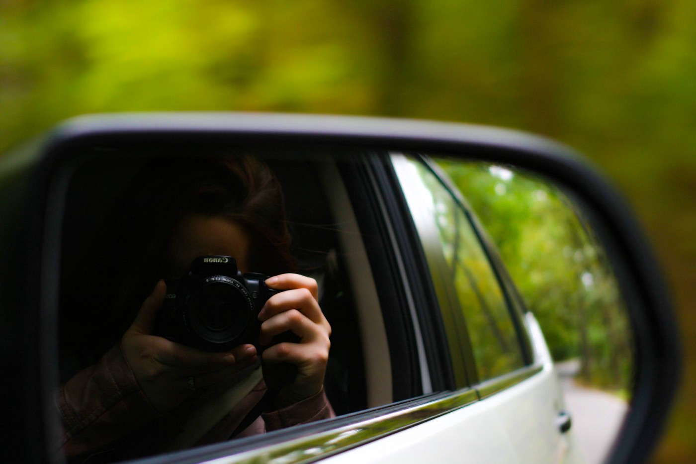 woman in a car taking a picture with a camera using the reflection from the rear view mirror