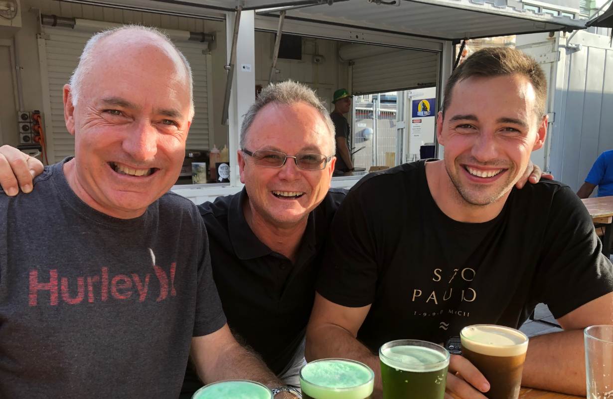 Jako with two older people smiling, green colour beers in front of them