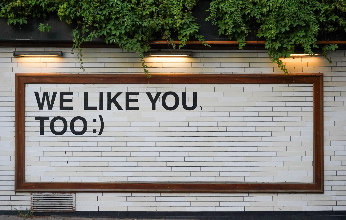 """Billboard on a brick wall with the words, """"WE LIKE YOU TOO:)"""""""