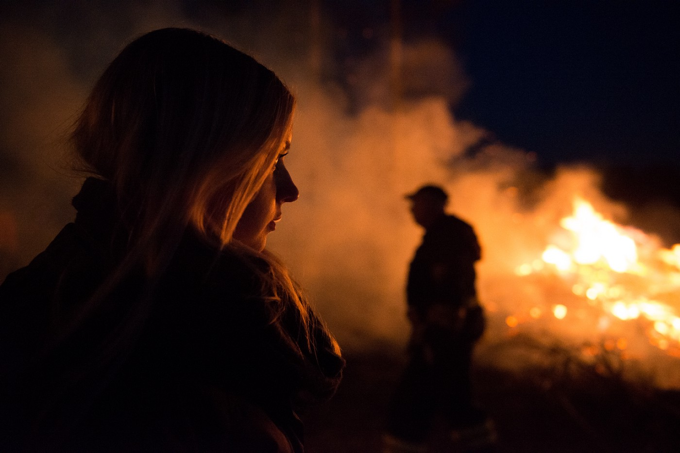 Side view of a young woman's face with fire raging in the back ground