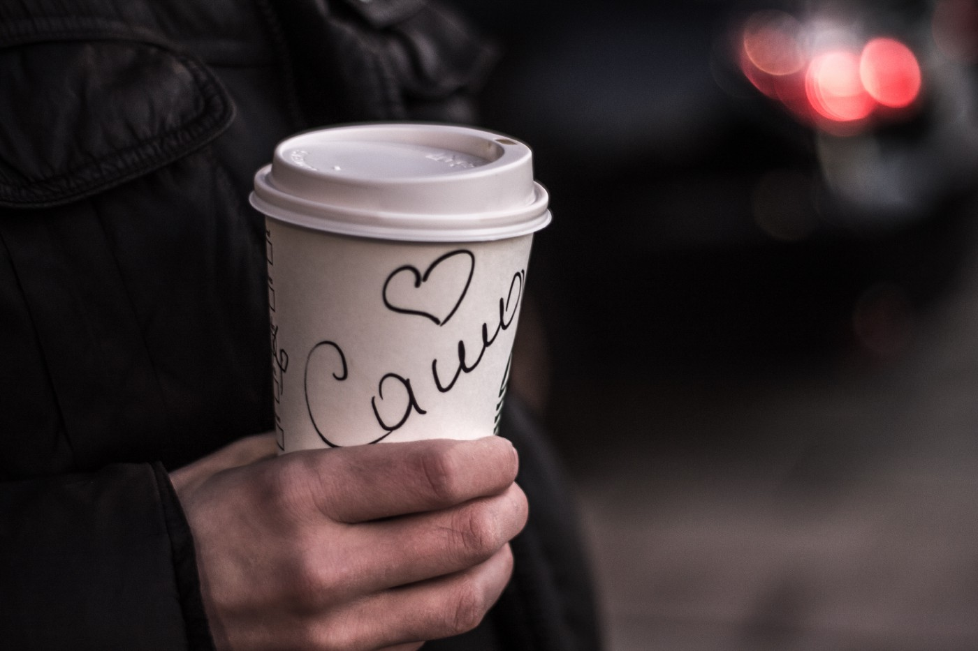Hand holding a coffee cup with a first name scribbled on it