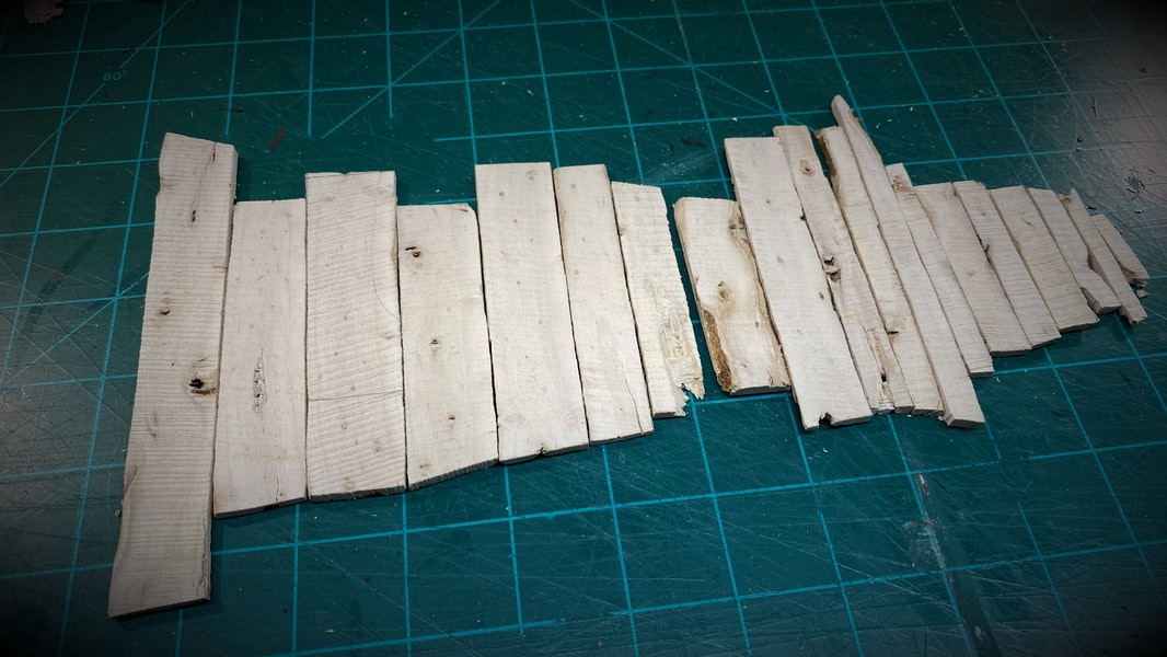 Thin wood planks lined up on a green cutting mat.
