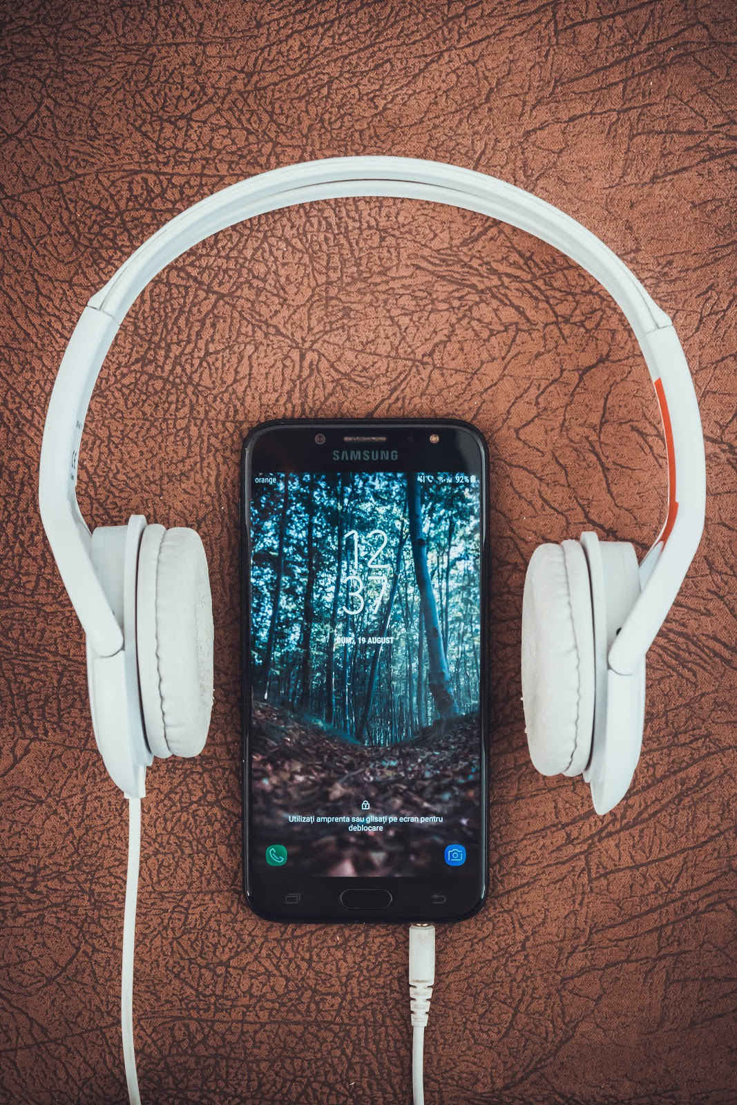 Smart phone on a table between over-ear headphones. The screensaver image is of a forest.