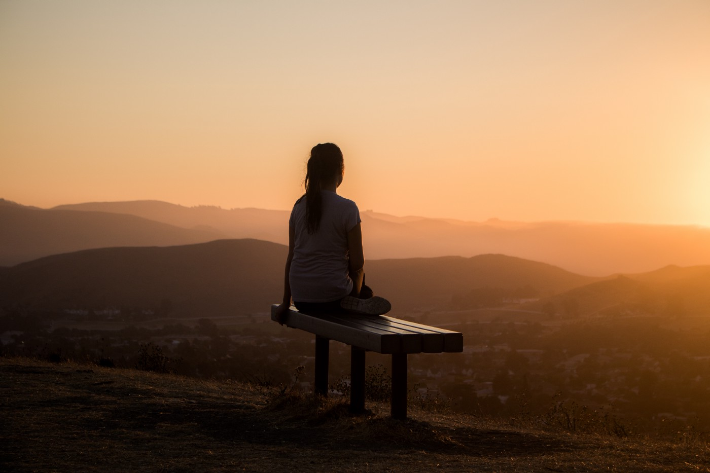 A picture of a young woman sitting on a bench and looking into the sunset in a beautiful mountainous area.