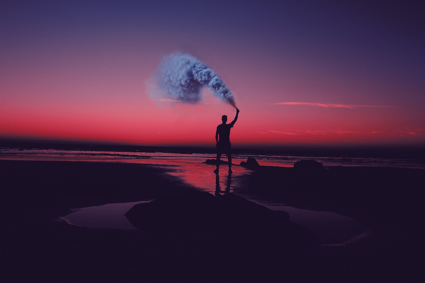A person holding a smoke device looks toward the red sky while standing at the seashore.