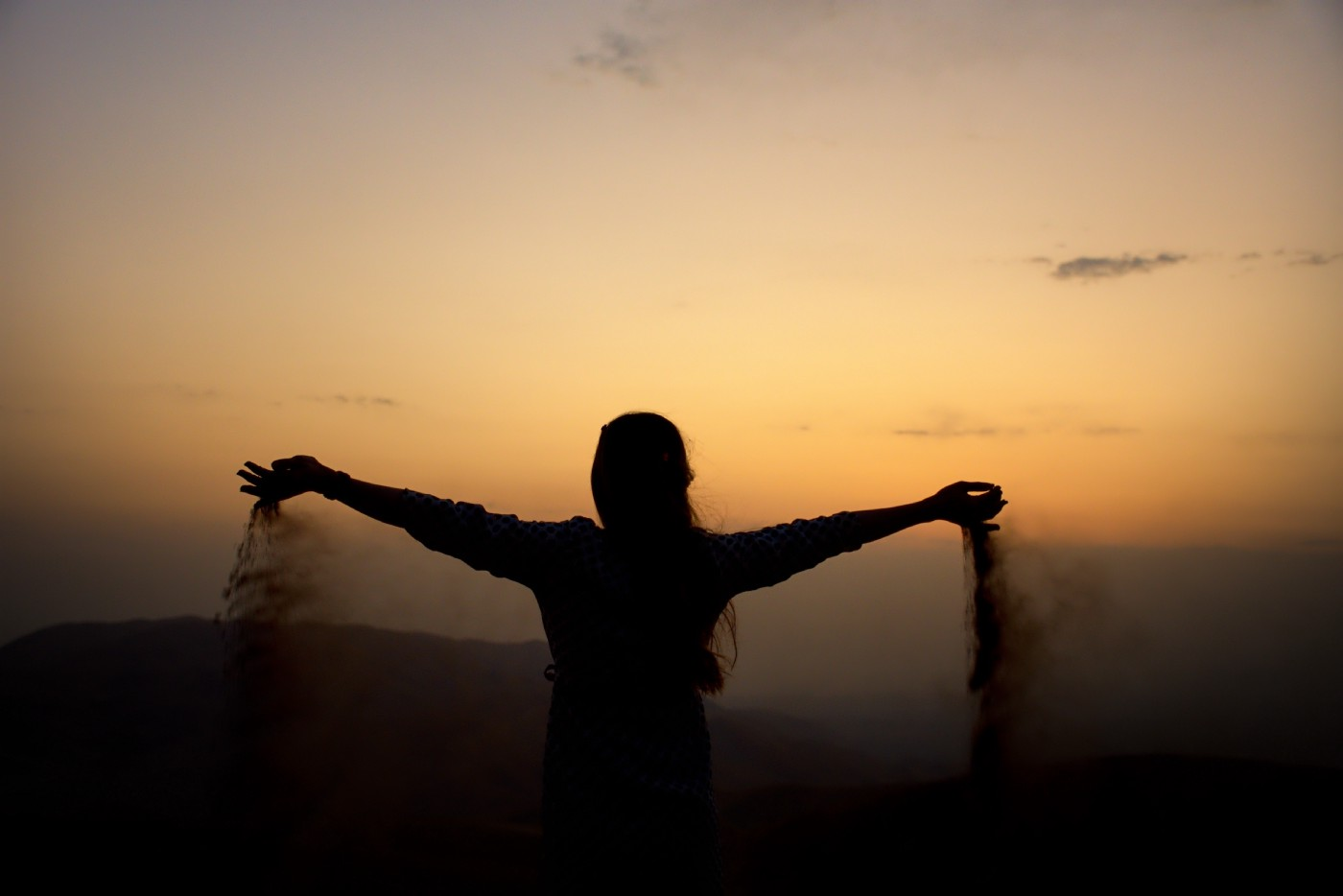 Silhouette of a person holding their arms out wide and letting what appears to be sand fall through their fingers.