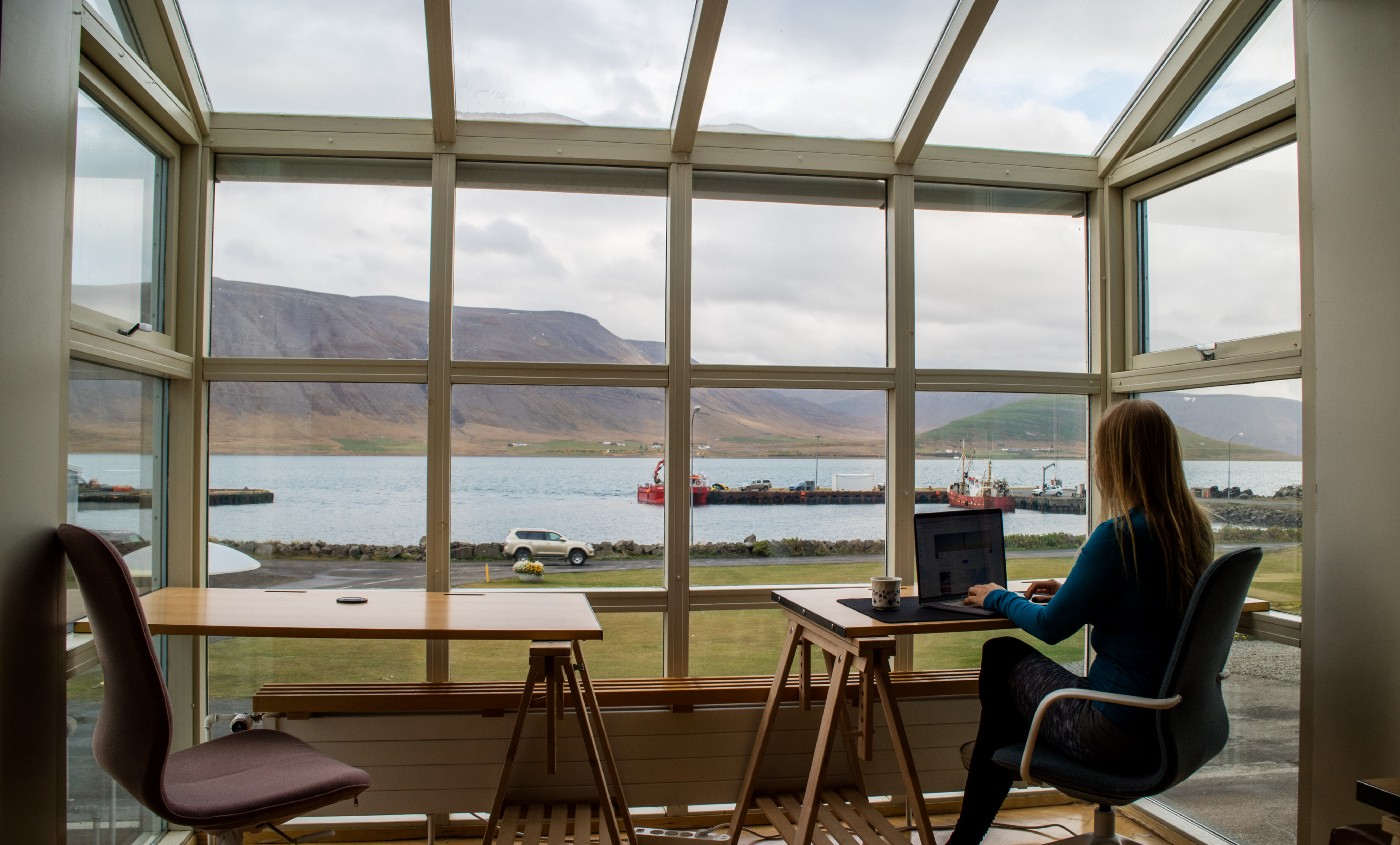 Girl sitting at a desk in front of a large window with a sea view