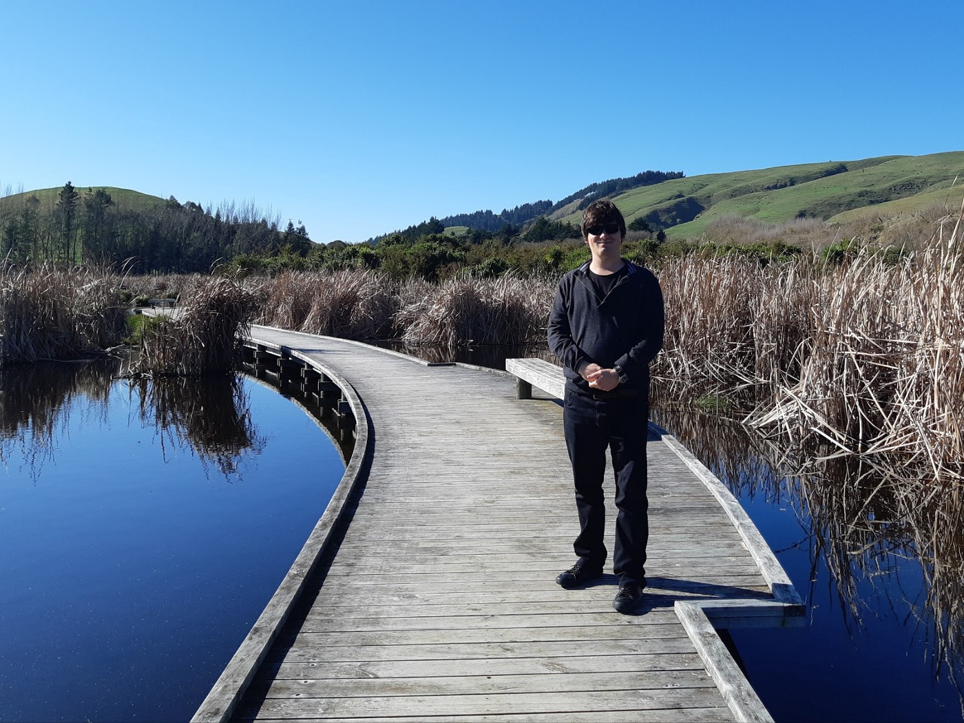 Jake standing on a boardwalk that goes through a wetland