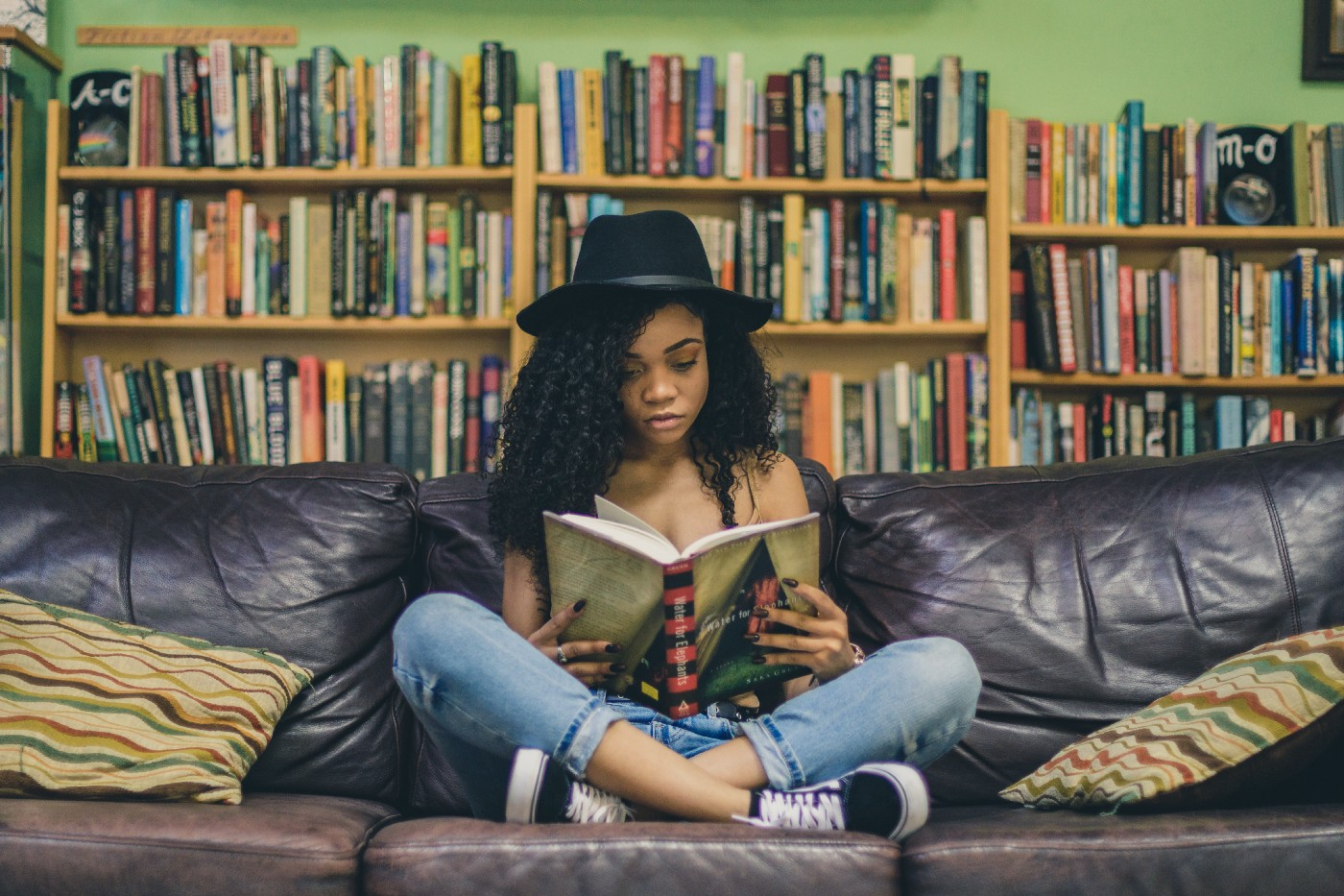 Young girl sitting on couch cross-legged. She's reading a book that is open on her lap.