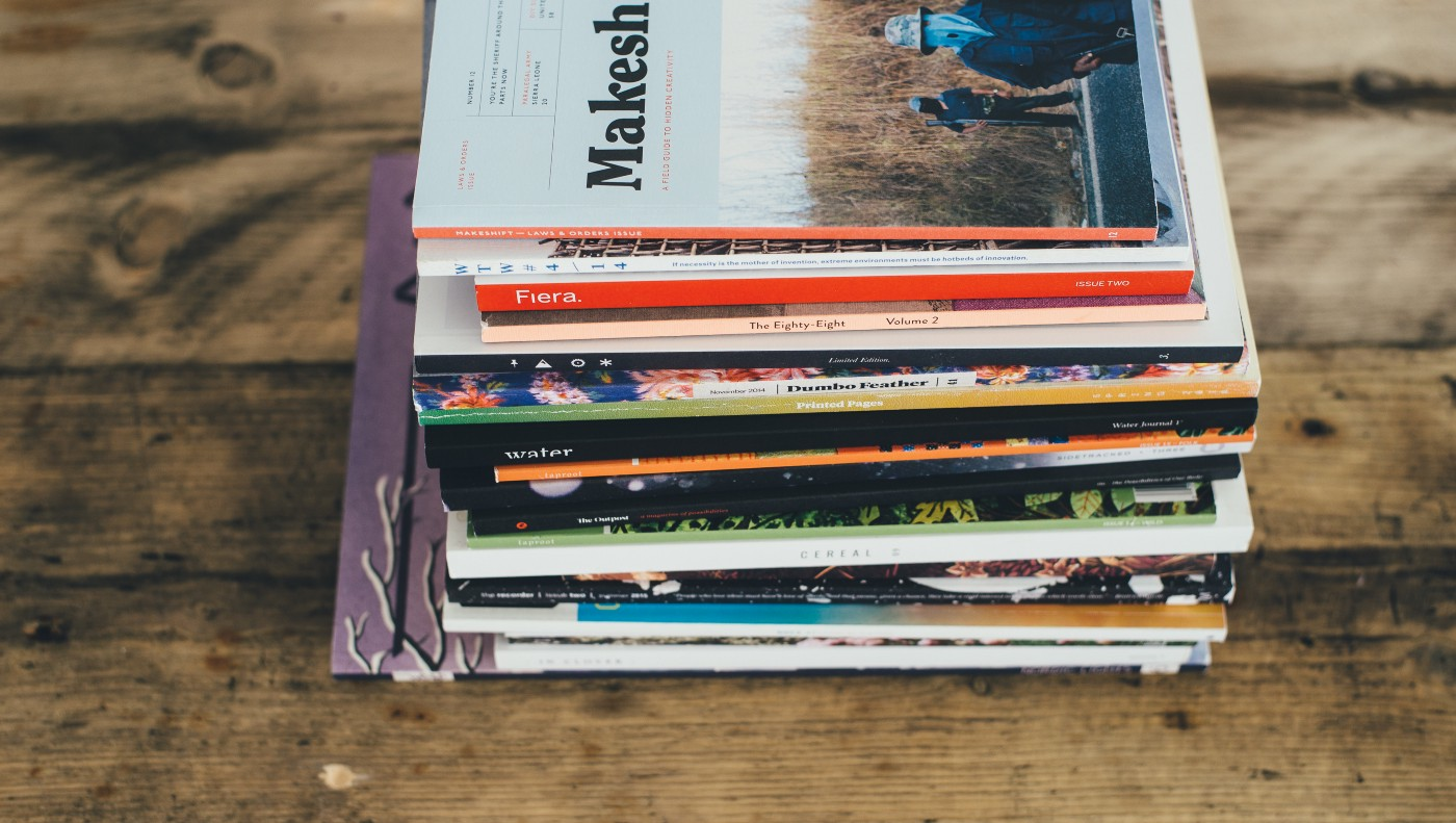 A stack of well-worn magazines sits on a wooden desk.