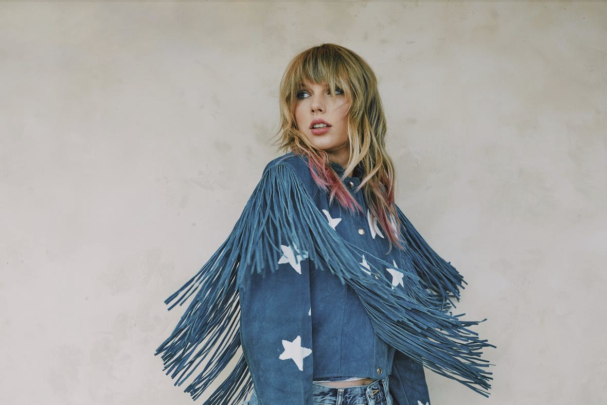 Taylor Swift looks coyly aside before a neutral background, wearing a fringey denim top with star patches