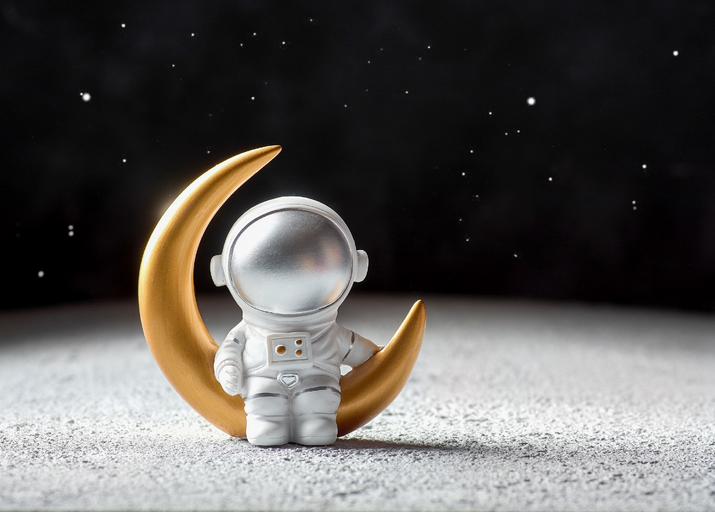 the image is that of a toy astronaut sitting on the shape of a crescent moon. The background is a dark starry sky. It appears that both are blow up pieces. the astronaut is in silvery white and the moon is golden