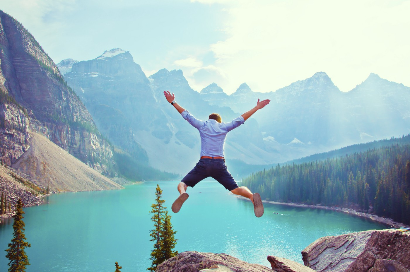 man jumping into a mountain lake from a high ledge