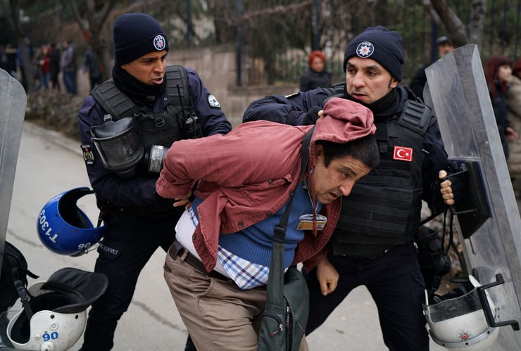 Anti-riot police detains a journalist during a police raid to break up protest at Ankara University in early 2017.