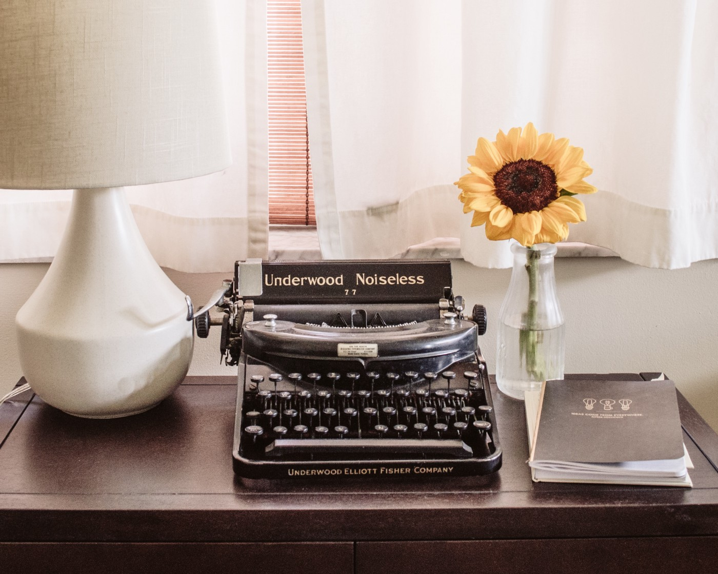 A typewriter, a white lamp, a sunflower in a vase, and a notebook