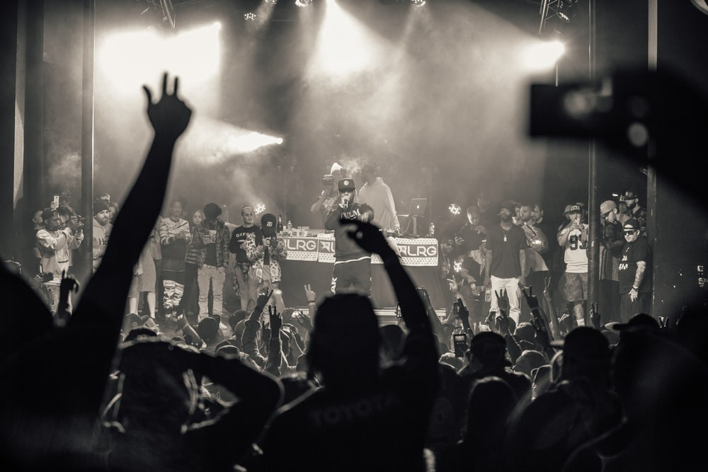 Black and white image of a crowd with hands in the air at a hip hop concert