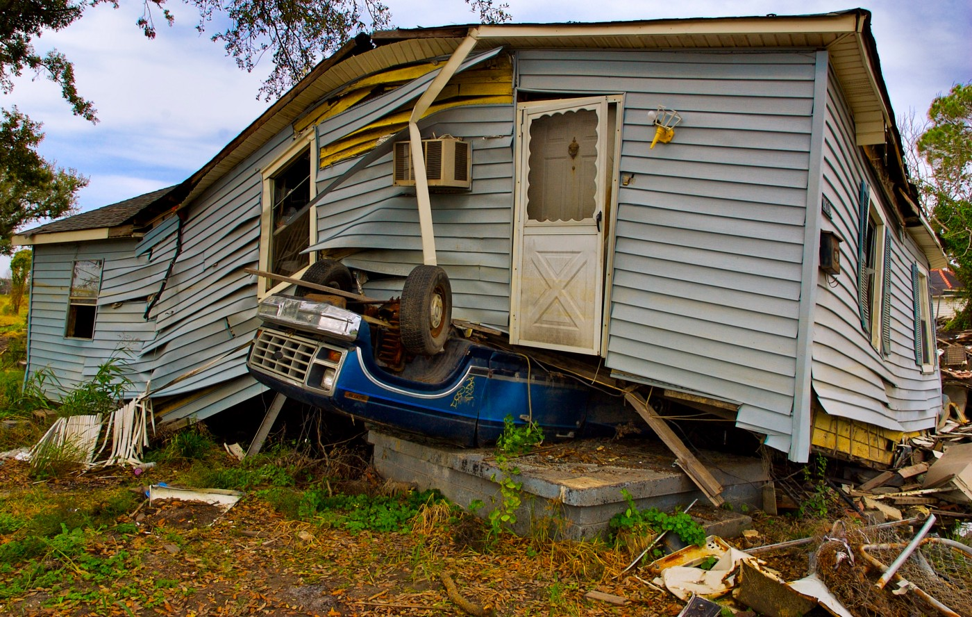 A light blue storm-ravaged house that has been shaken from its foundation sits on top of a royal blue upside-down vehicle.