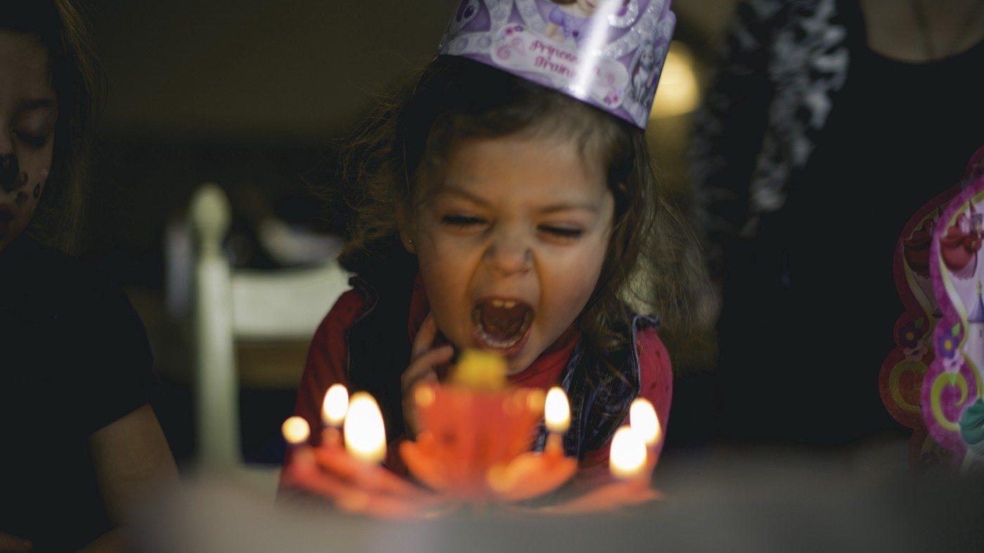 Little girl in party hat sitting in front of cake with candles about to blow them out