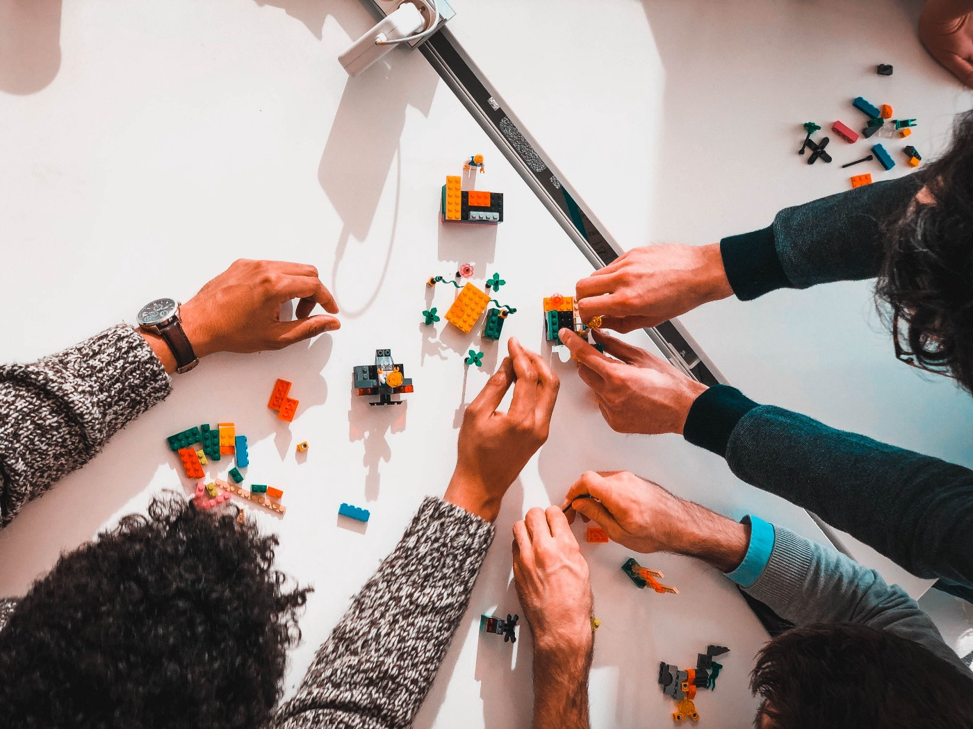 Picture of 3 people's hands building and playing with Legos