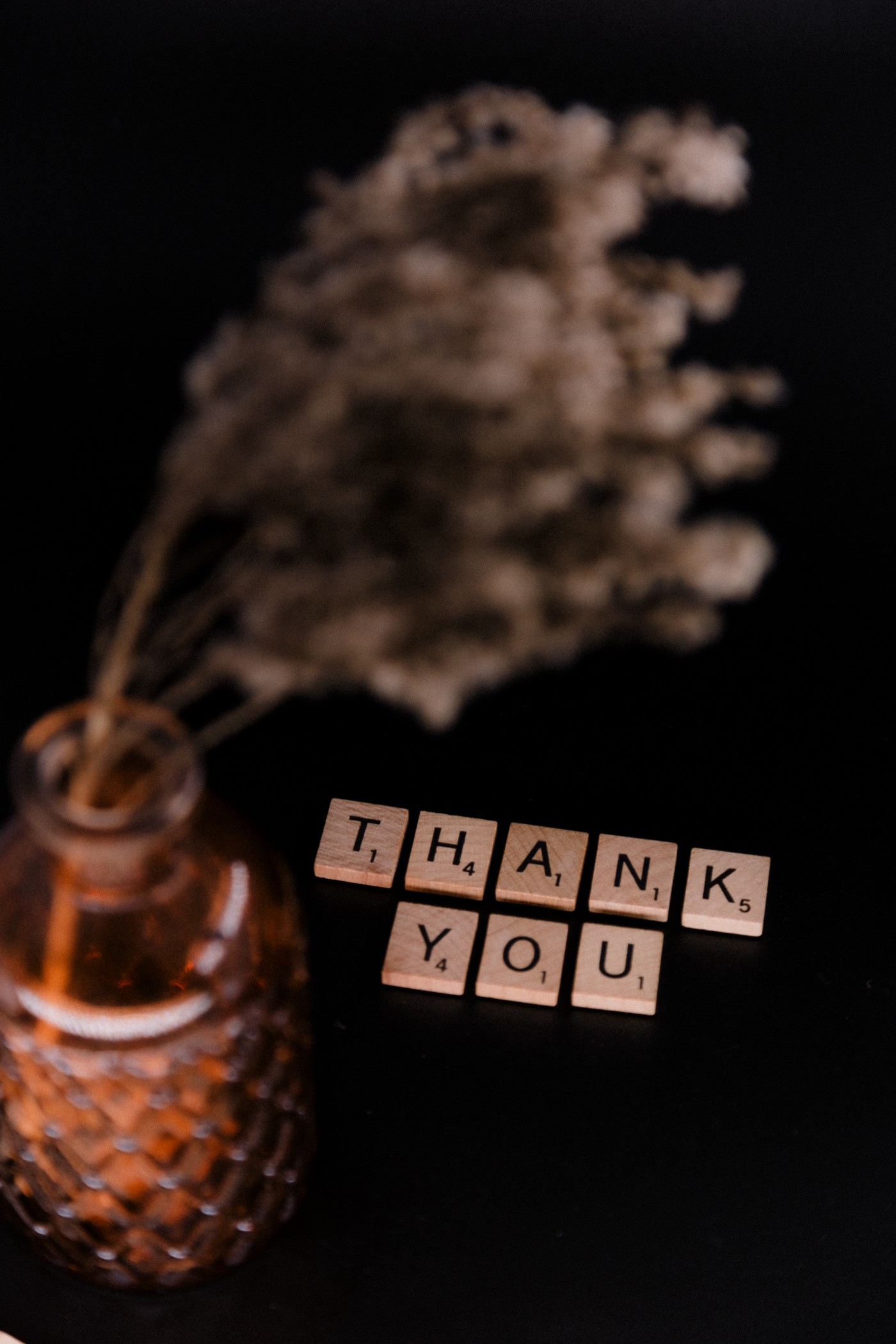 The image focus on a set of scrabble tiles that spell out the words THANK YOU