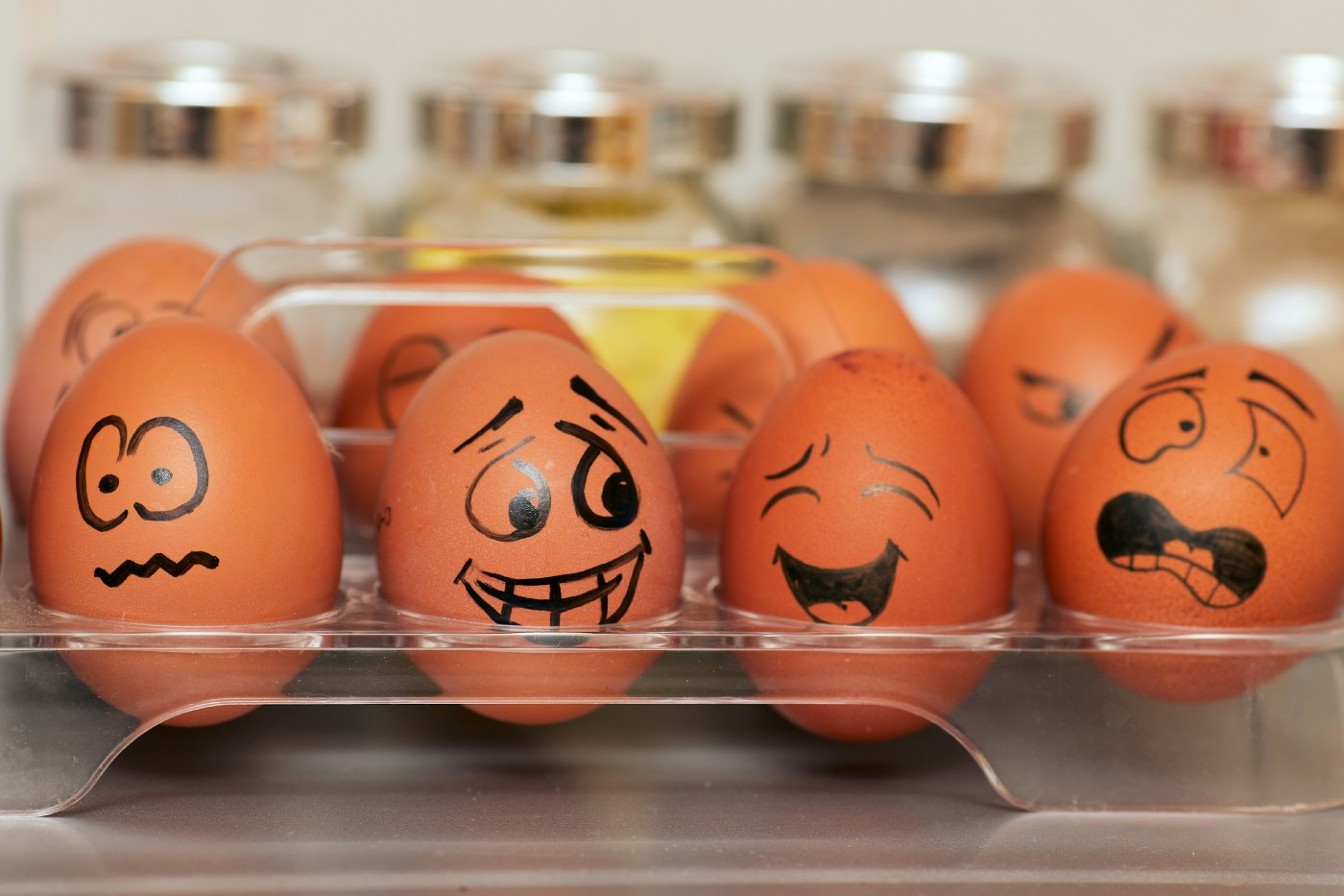 Four eggs with various emotive faces drawn on with sharpie