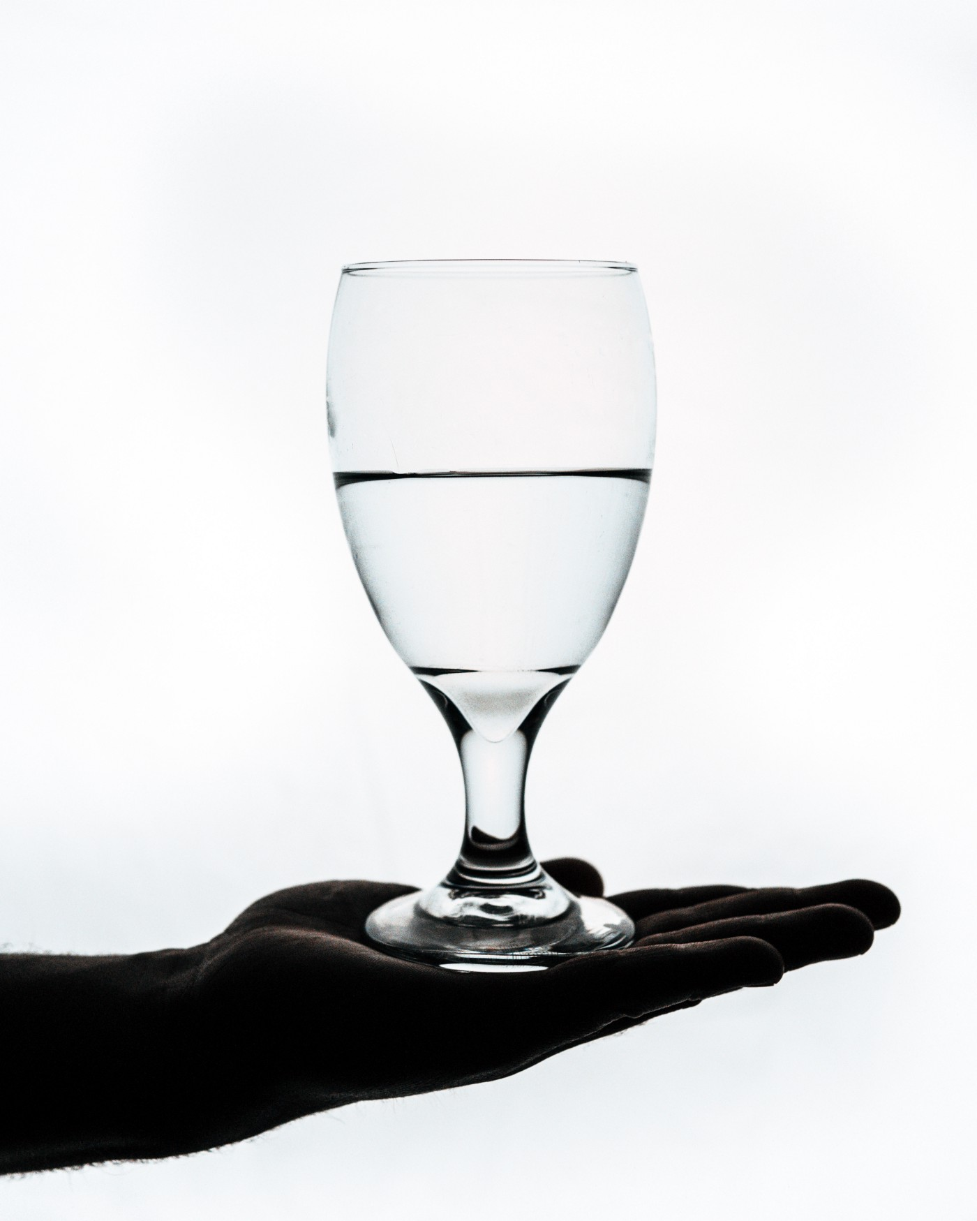 A dark hand open palm up while holding a wine glass. The Glass is half filled with water.