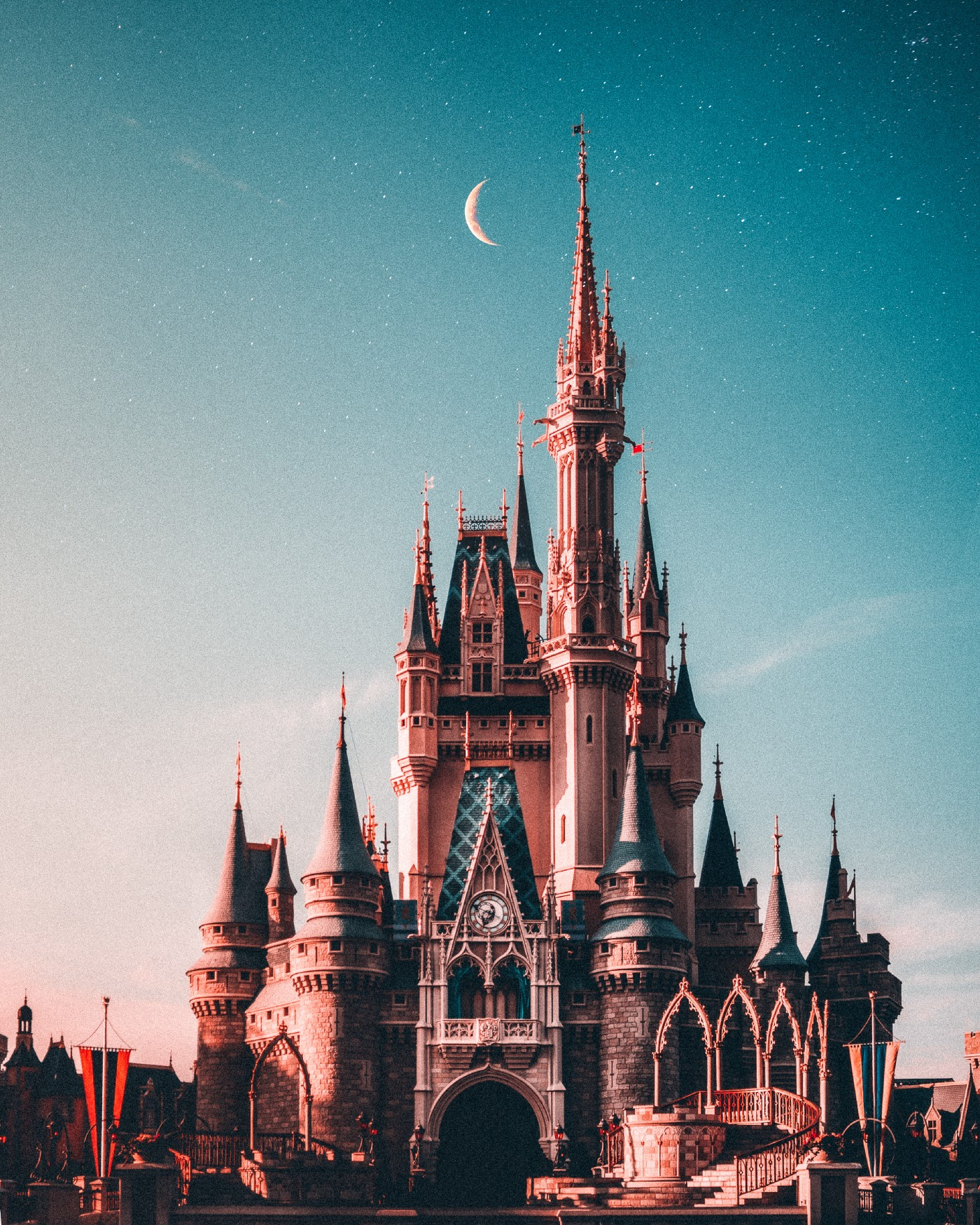 Big castle in Disney World at dusk with a crescent moon behind