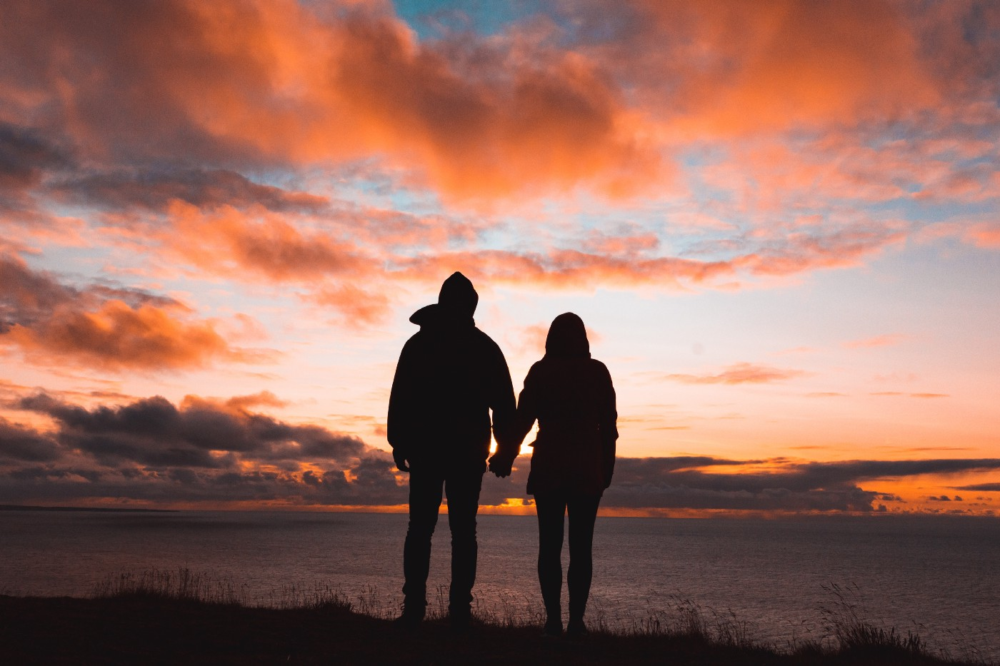 The silhouette of a couple holding hands while looking out across a body of water at a beautiful sunset reflected in a cloudy sky