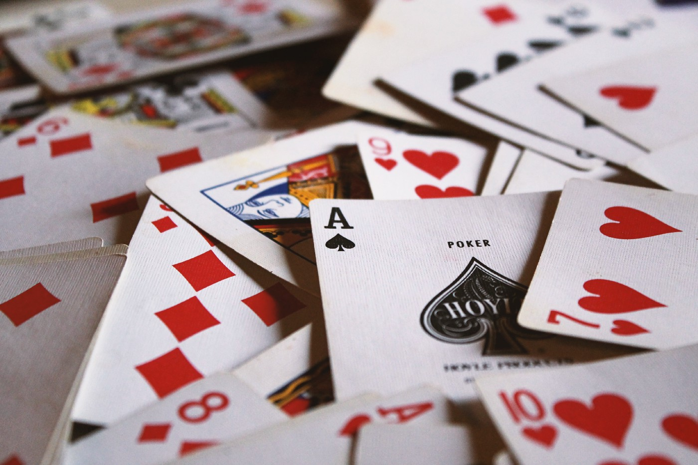 A deck of cards is spread across a table. On top, an ace of spades is visible.