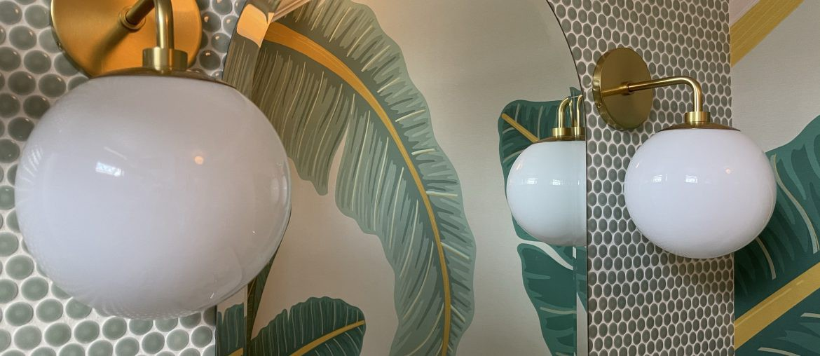 White globe wall sconces with brass finish frame an arched bathroom mirror reflecting tropical palm frond wallpaper.