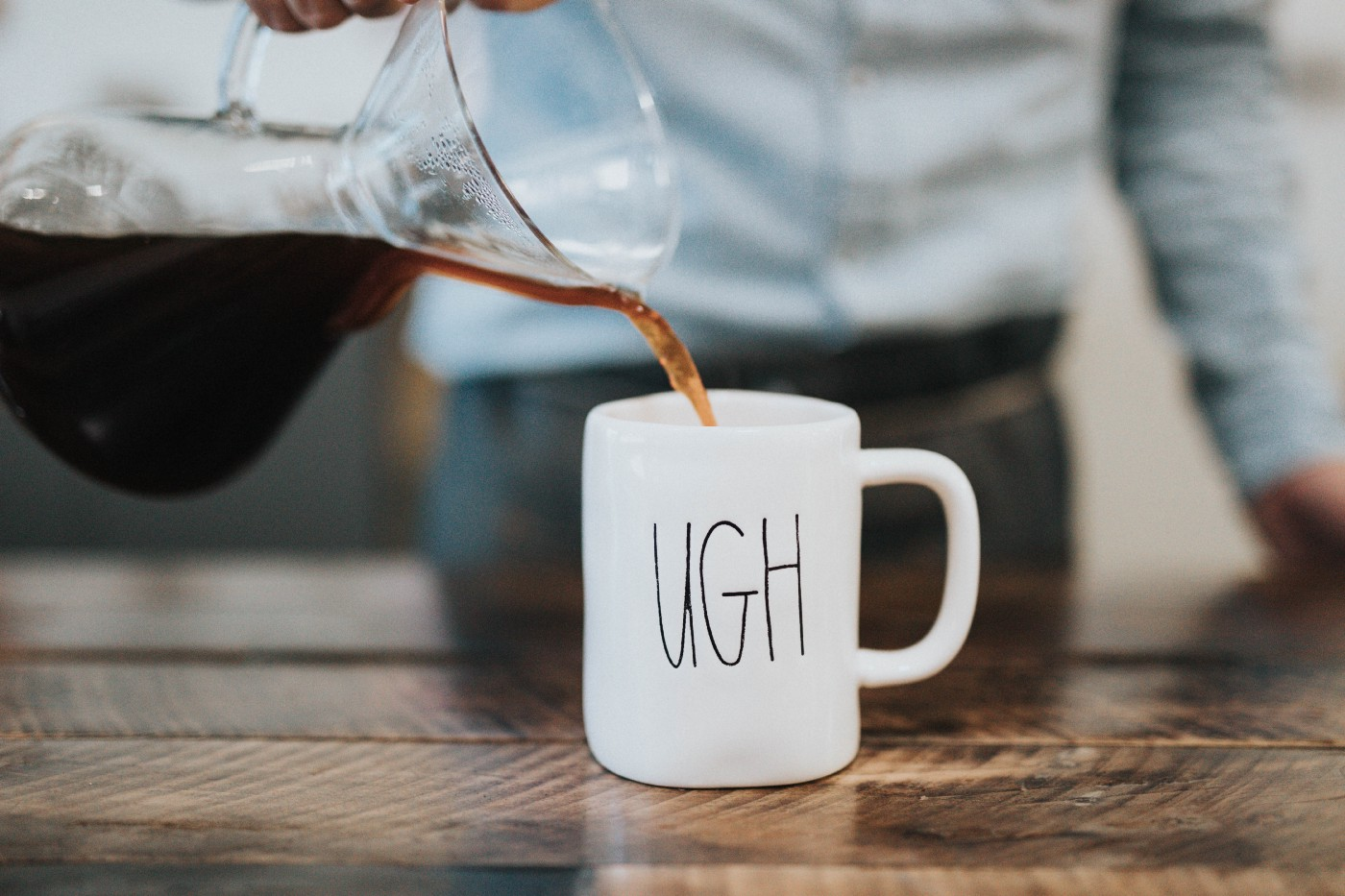 """Coffee being poured from a glass jug into a mug with """"Ugh"""" on it"""