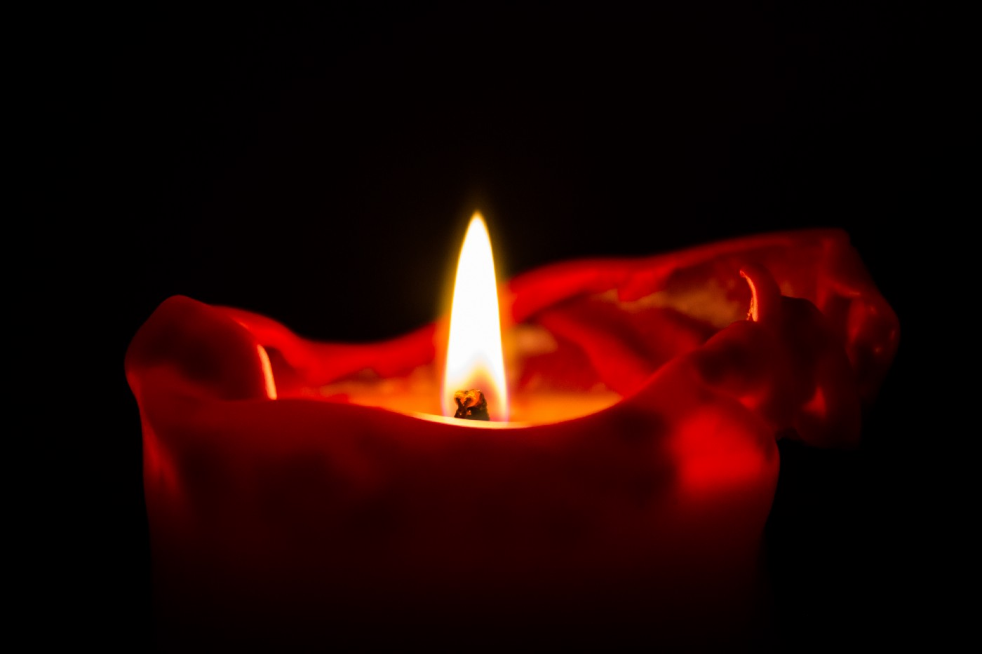 the image is taht of a single red lit candle on a black background