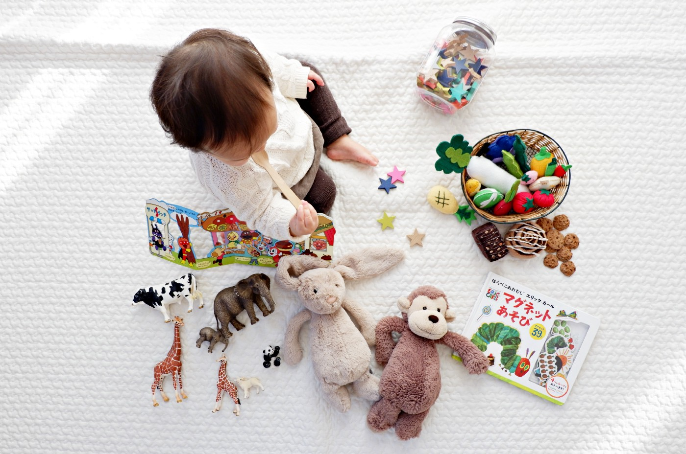 young toddler on white blanket deciding what toy to play with