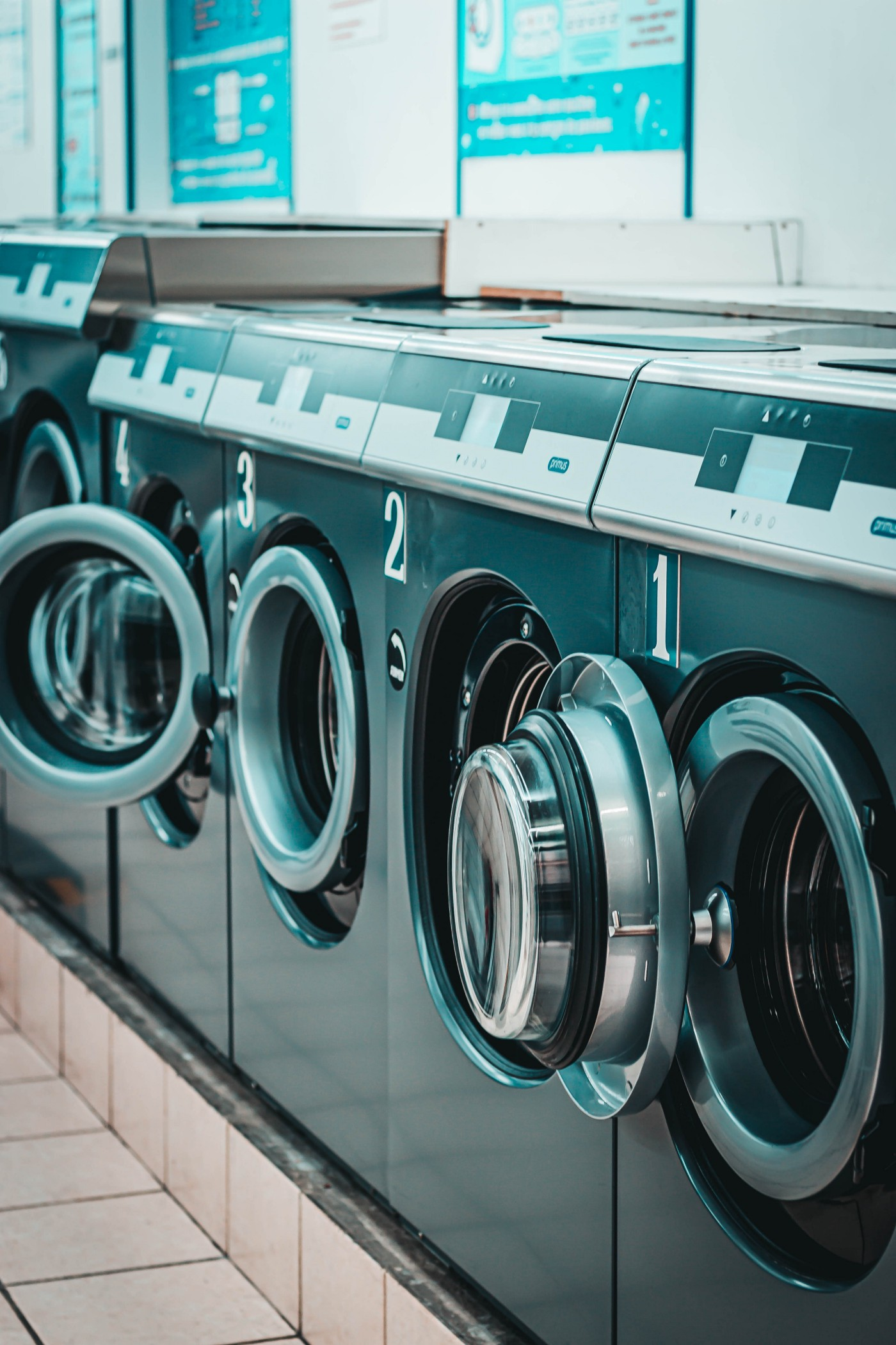 a row of washing machines in a laundry mat. a row of dryers in a laundry mat