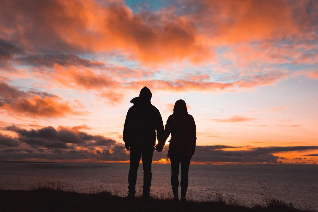 a couple holding hands watching a sunset