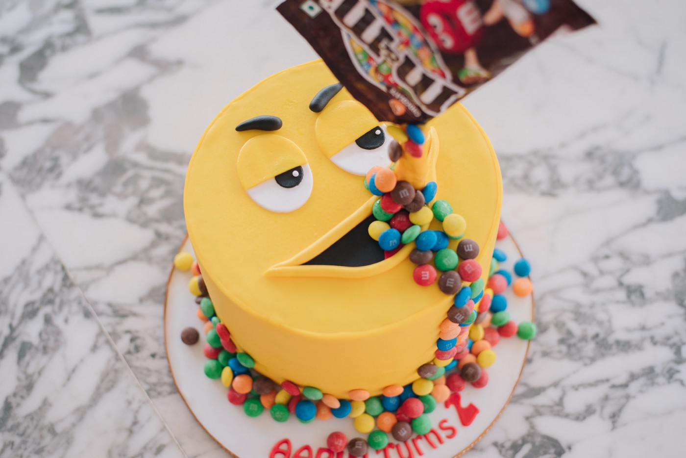 A yellow cake has a face. Its mouth wide open. M&Ms are poured in its mouth, the perfect Libertarian dilemma.