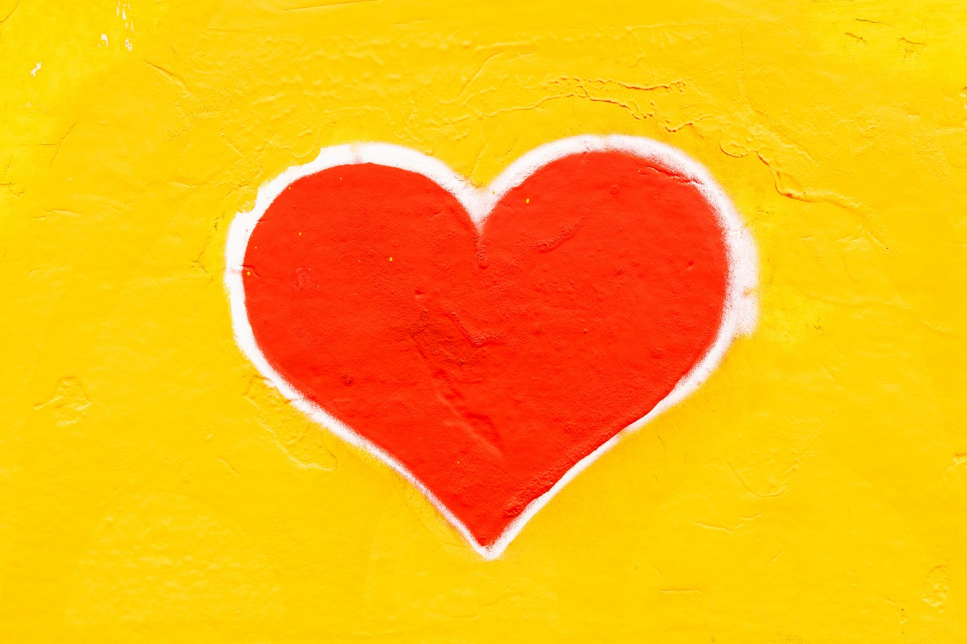 Red heart, with a white outline, painted on a bright yellow, stucco, wall