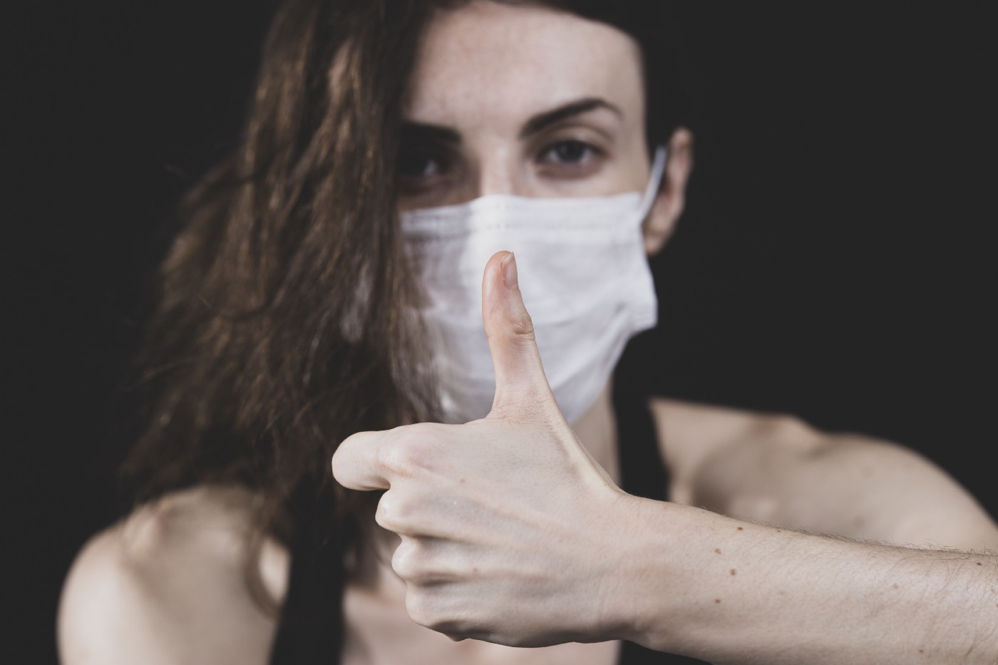 A woman in a blue disposable face mask makes a thumbs-up gesture.