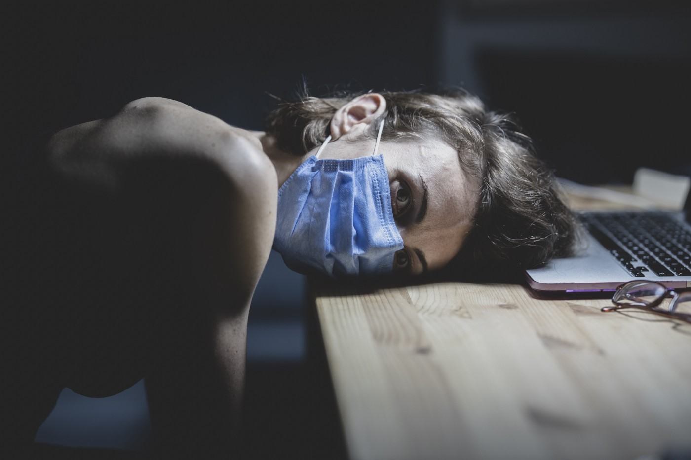 A girl wearing a mask is keeping her head on a desk near her laptop, looking worried.