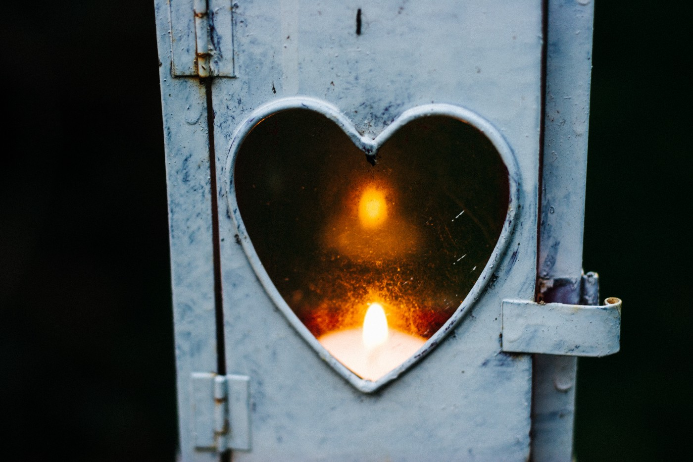 A small metal door with heart-shaped window and a candle glowing on the other side of it