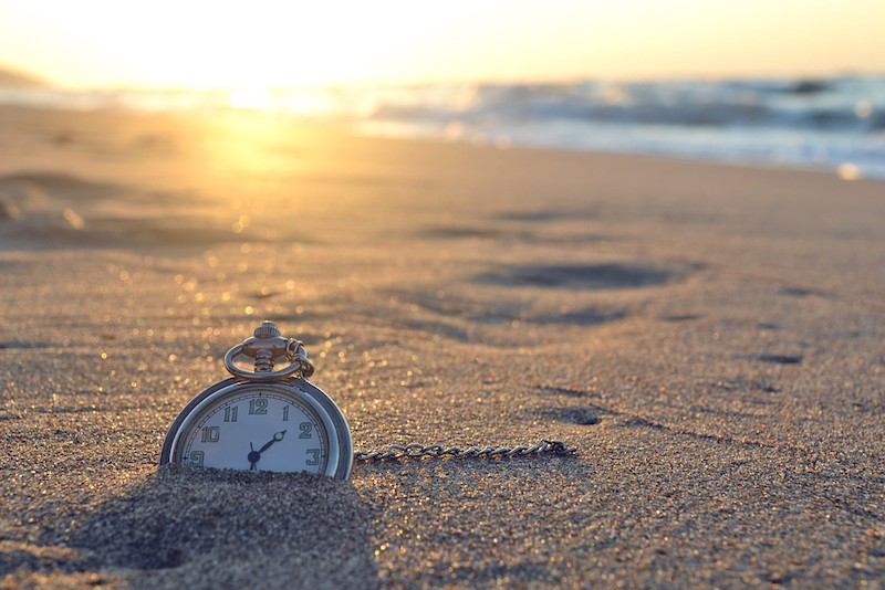 An old-fashioned watch buried in the sand