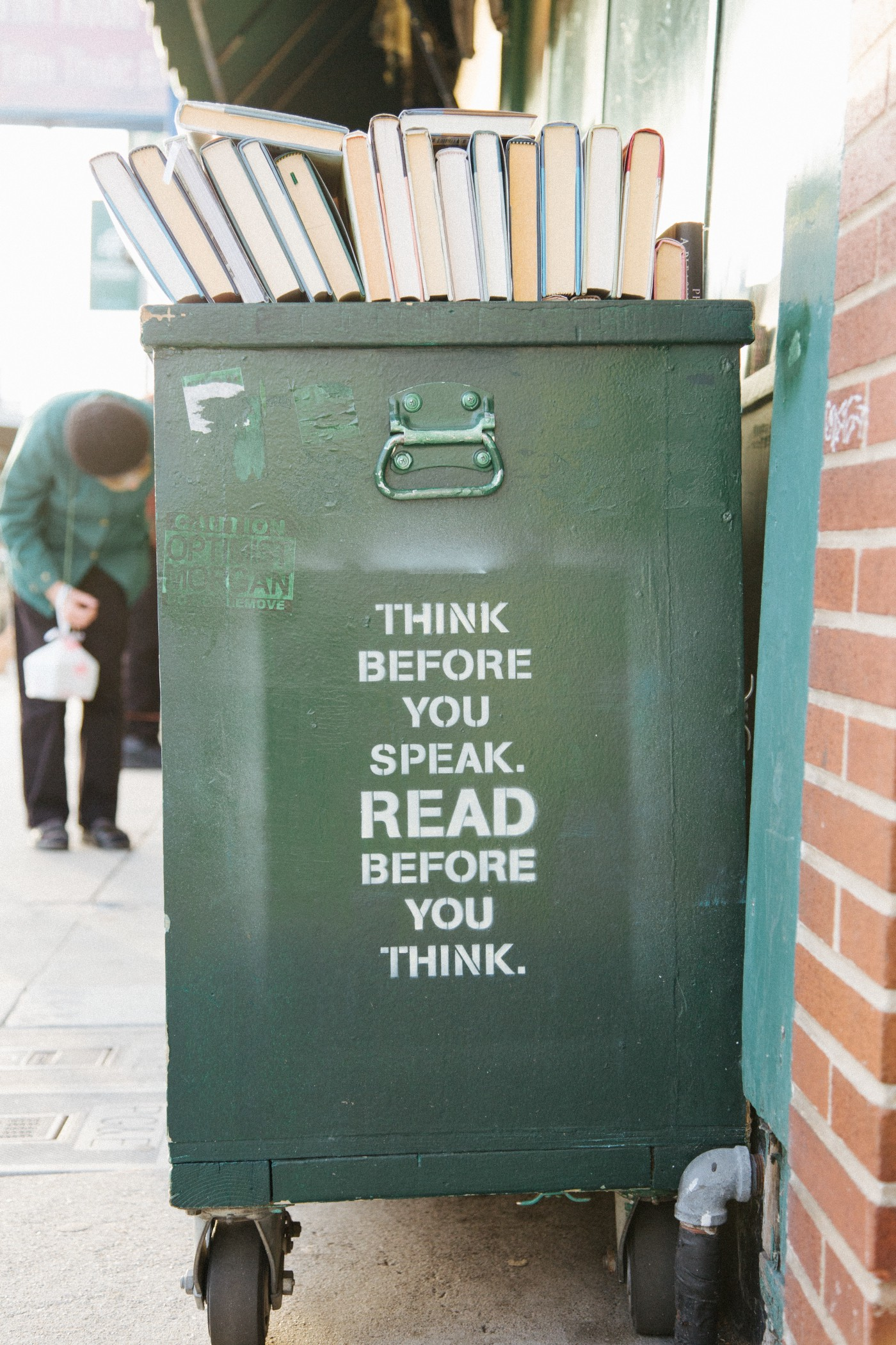 """Dumpster bin with books on the top, with the quote on the side 'Think before you speak, read before you think"""""""