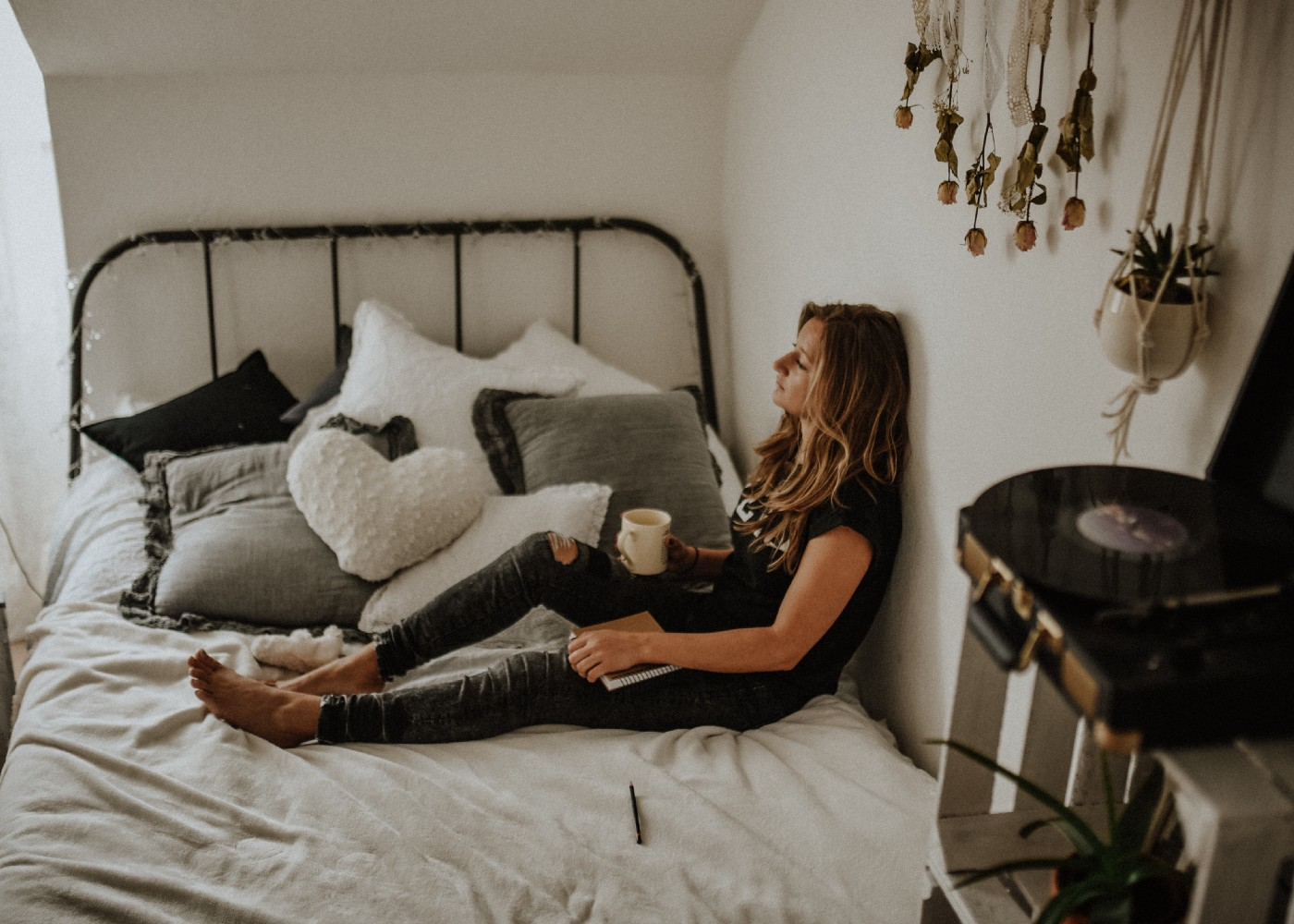 A woman practices self-care and relaxes on her bed.