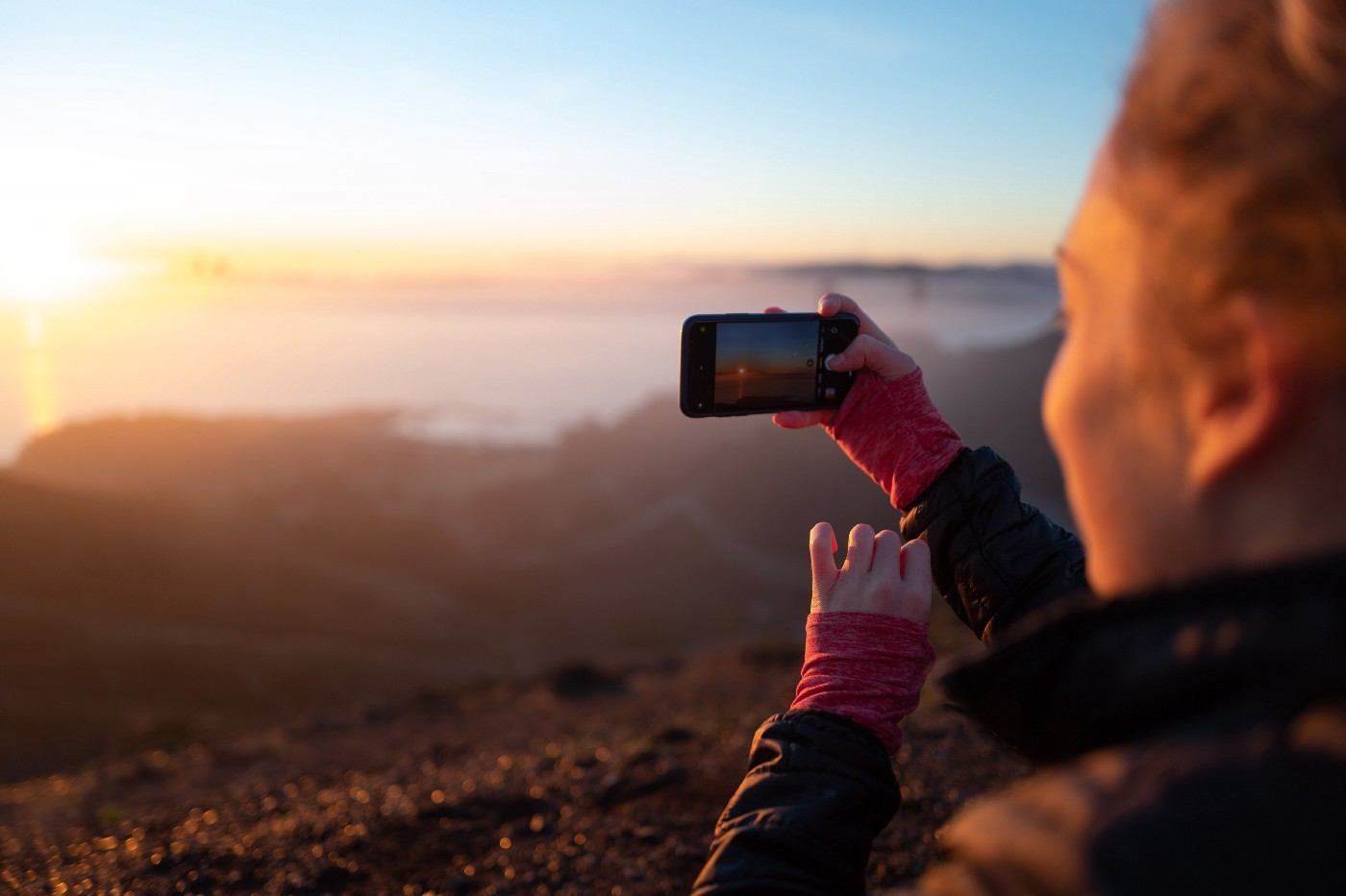 A woman taking a photograph with her smartphone