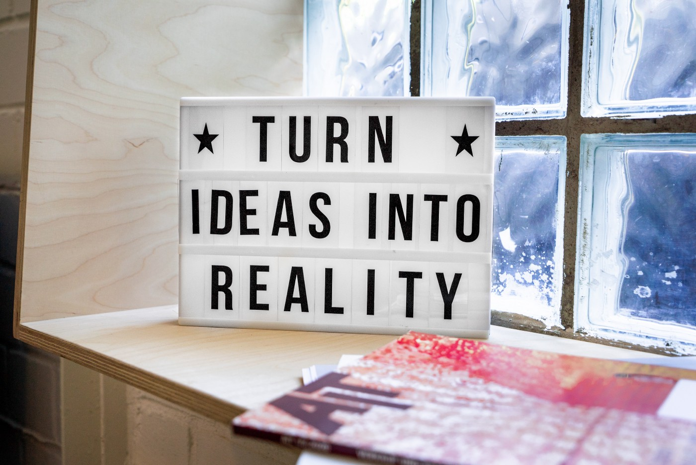 "A white sign on a wooden window sill that says in black letters, ""Turn ideas into reality."""